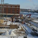 The five-story Smulekoff's building, seen along the Cedar River in February 2015, will be sold by the city for redevelopment. Work on the 11-story CRST International building headquarters continues in the foreground. (photo/Cindy Hadish)